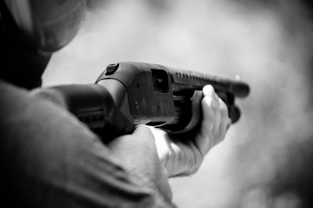 Close-up black and white image of someone holding a shotgun at a firing range