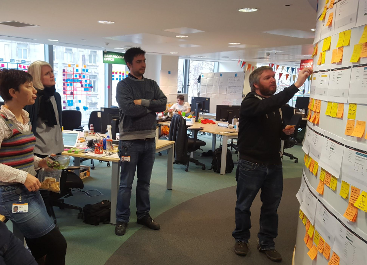 Photo of GOV.UK Notify team at a playback session in front of an agile wall with post-its on