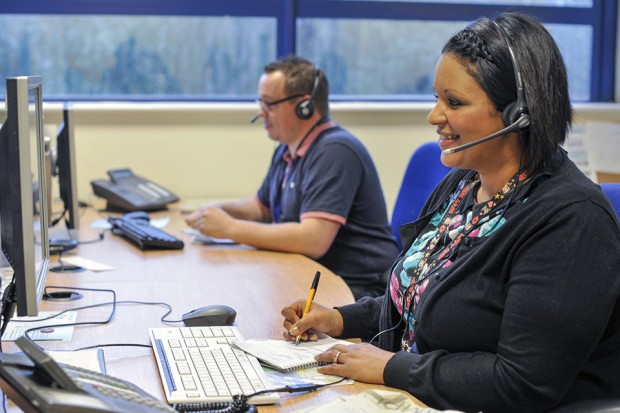 Photo of 2 contact centre advisers with headsets on, sat at desktop computers