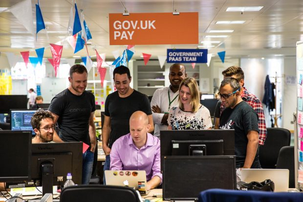 Photo of the GOV.UK Pay team gathered at a computer screen to watch Till Wirth make the first debit card payment using the GOV.UK Pay product.