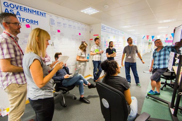 A group of GDS staff hold a discussion around the GaaP roadmap wall