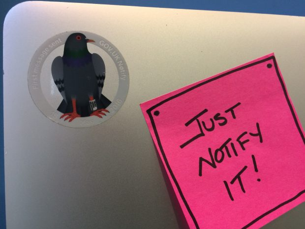 A picture of a laptop cover with a sticker of a pigeon and a post-it note reading 'Just notify it!'