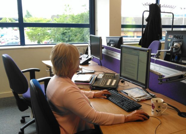 Photo of a webchat advisor looking at a desktop computer screen wearing a headset and using a mouse