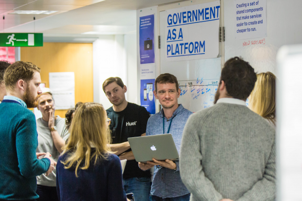 The government as a platform team stand up and discuss team matters in front of a sign that reads 'government as a platform'