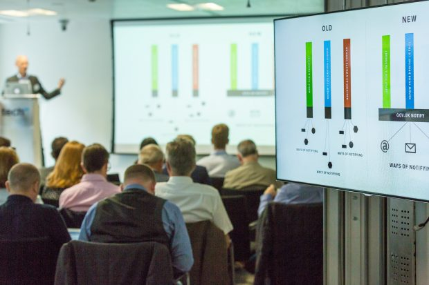 Photo of an event at which Government as a Platform components are showcased. The audience are facing screens showing a diagram of how GOV.UK Pay works