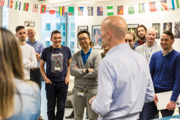 A group standup with several attendees laughing